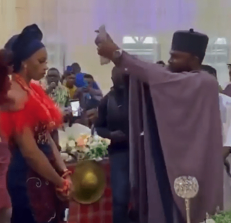 Bride refuses to smile as her husband sprays her Naira notes at their traditional wedding (Video)