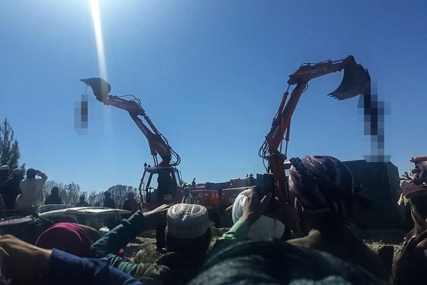 Taliban hang corpses of three men from diggers after they were publicly executed