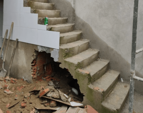 Woman dead body found buried in a concrete wall beneath a staircase