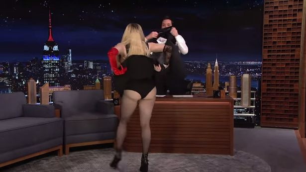Madonna goes wild on TV as she pulls up her dress to expose her underwear, causing host Jimmy Fallon to cover her up with jacket