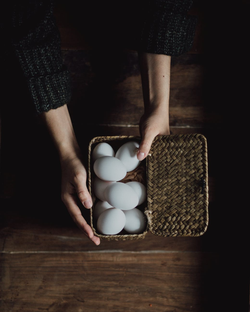 crop person holding chicken eggs in basket