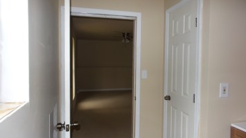 Unfurnished Living and Kitchenette Area from Bathroom Door