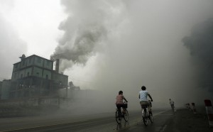 Yutian, CHINA: Cyclists pass through thick pollution from a factory in Yutian, 100km east of Beijing in China's northwest Hebei province, 18 July 2006. China's economy expanded at its fastest pace in a decade with growth of 11.3 percent in the second quarter, official data showed, exceeding expectations and possibly signaling the need for new cooling measures. AFP PHOTO/Peter PARKS (Photo credit should read PETER PARKS/AFP/Getty Images)