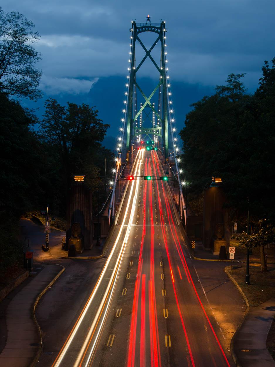 Cars drive across Vancouver's Lions Gate Bridge at dusk