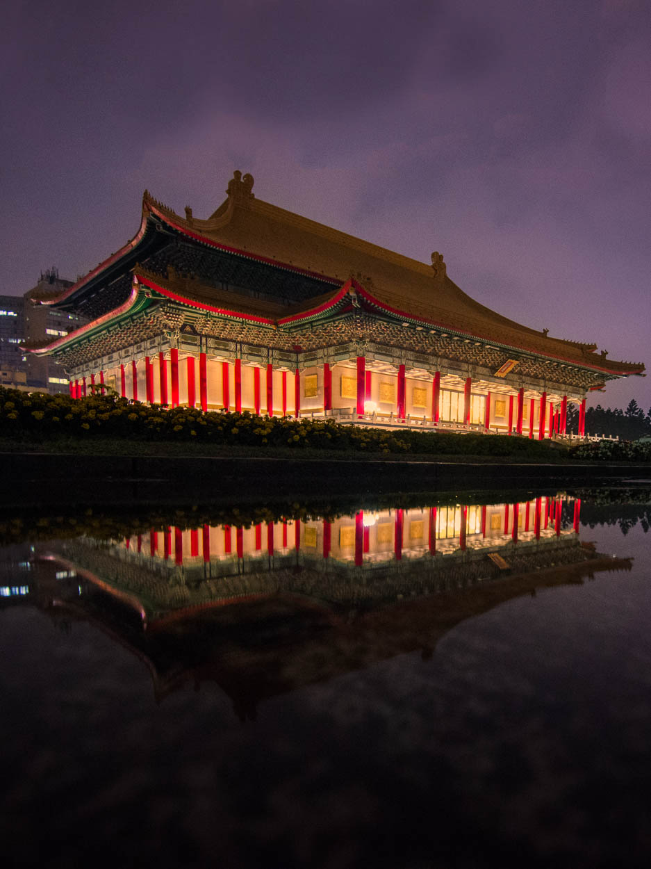 Taiwan's National Theatre is reflected in a rain puddle