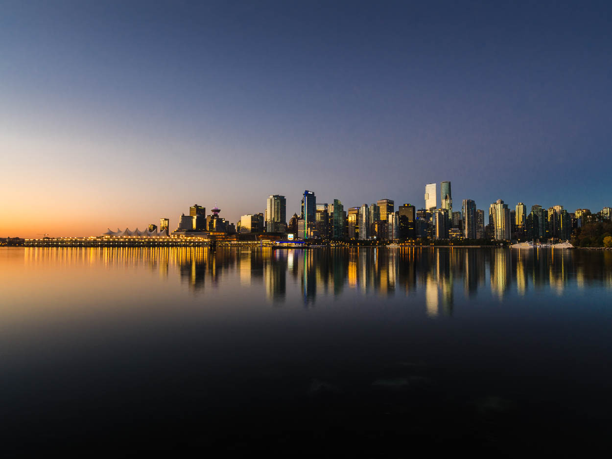 As sunrise approaches, downtown Vancouver is reflected in the waters of Coal Harbour.