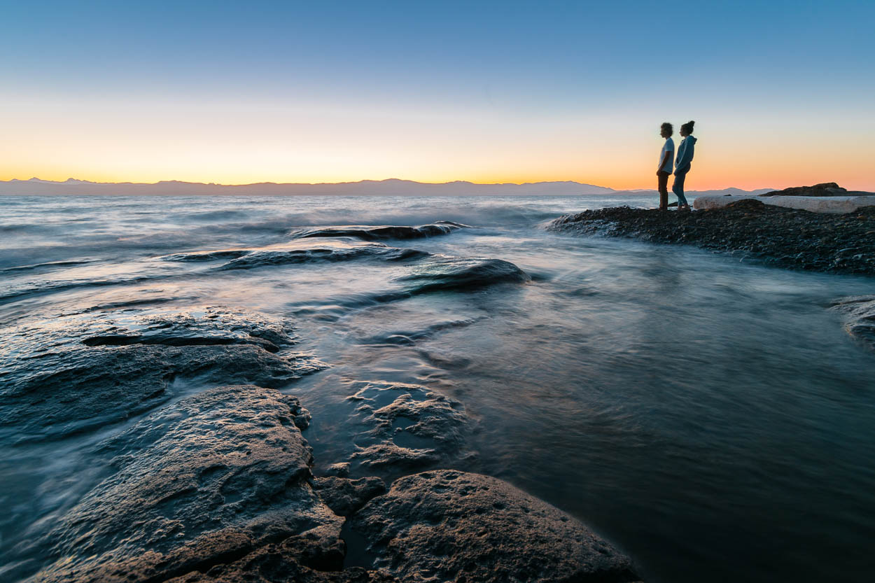 Two people watch the sunrise from Hornby Island Helliwell Provincial Park