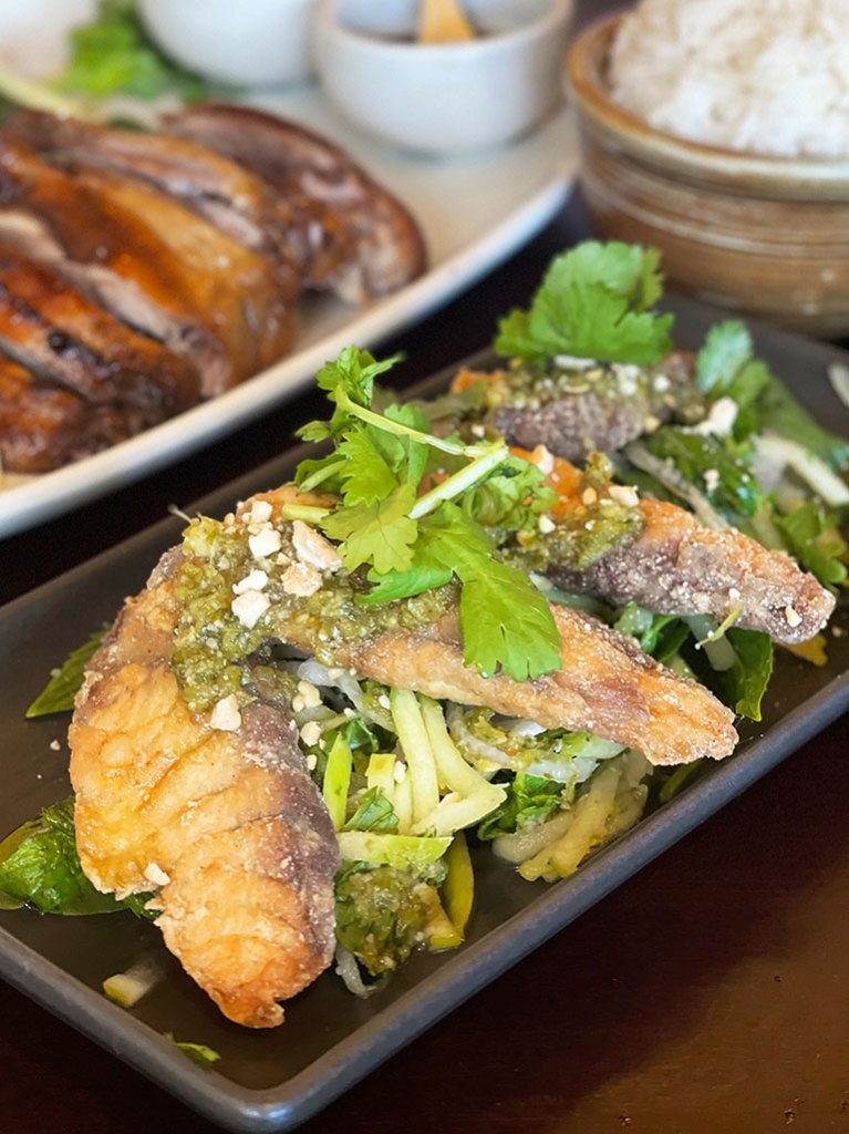 A plate of pan fried barramundi served with green Thai sauce and apple salad from Emily Taylor Restaurant & Bar