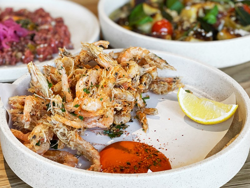A plate of whole, fried school prawns with fermented chilli aioli and lemon from Besk
