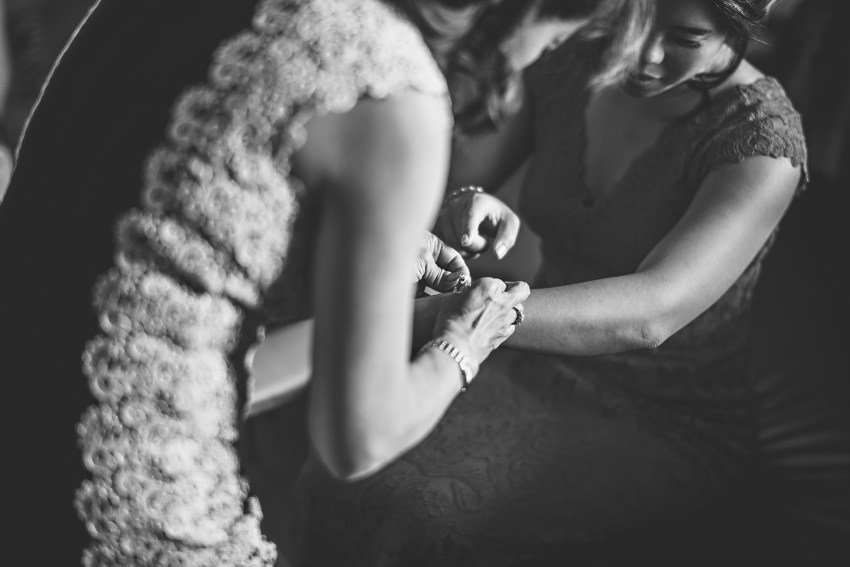 bride mother putting on jewelry