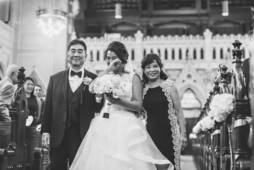 bride crying during processional with parents