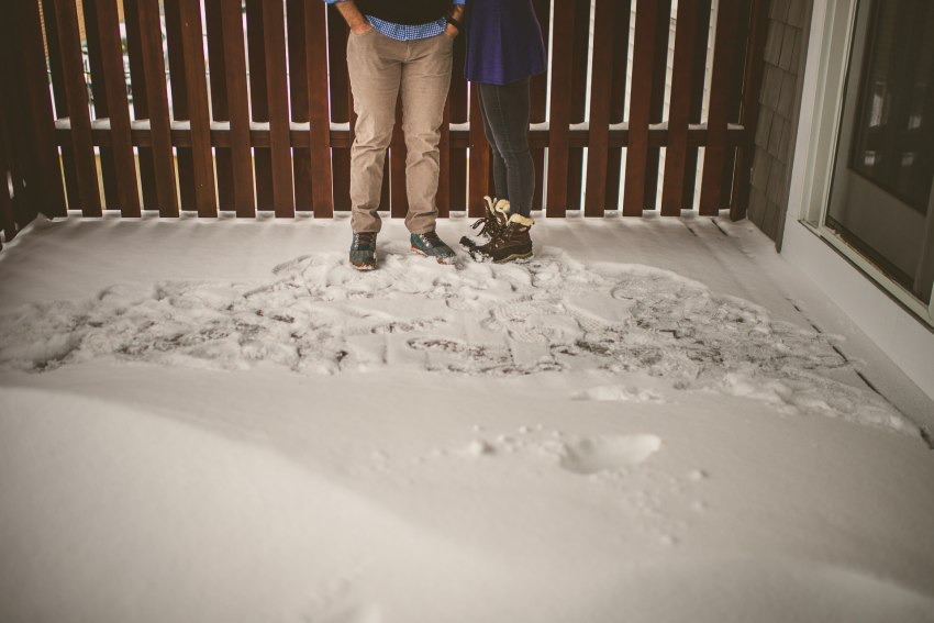 Engagement session on snowy balcony