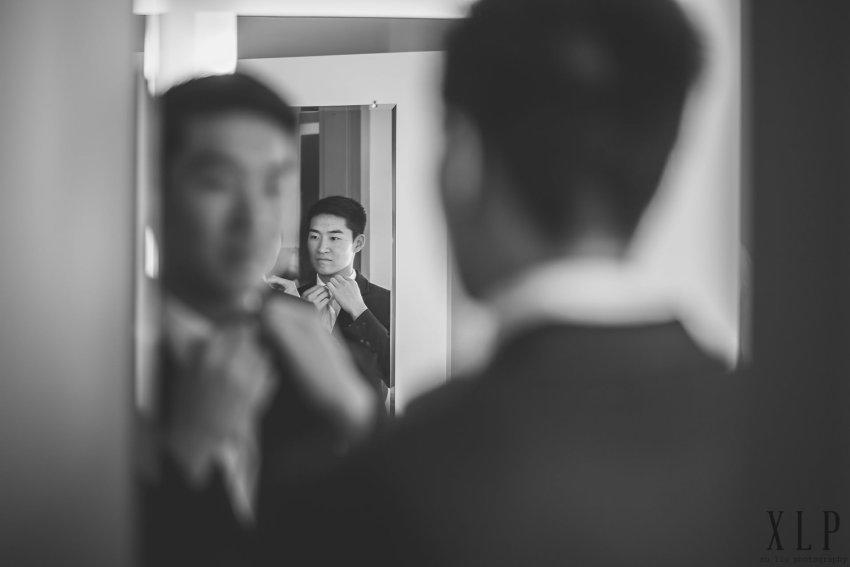 Groom tying tie reflection