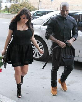 A somber looking Kim Kardashian receives a red rose from Kanye West as they head out in New York City
