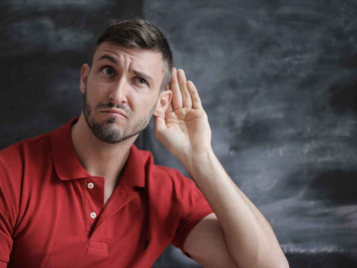 man in red polo shirt sitting near chalkboard