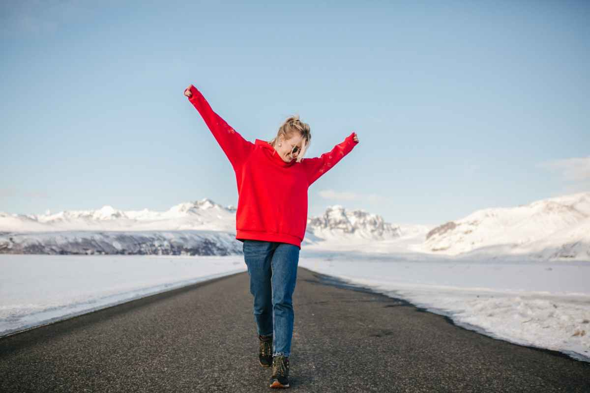 a woman stretching while walking on the road