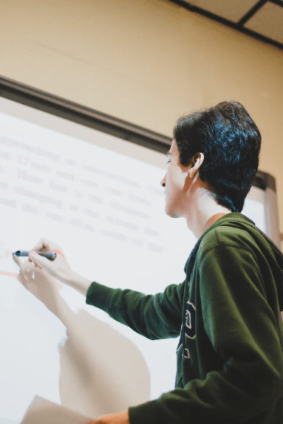 A teacher writing on a white board