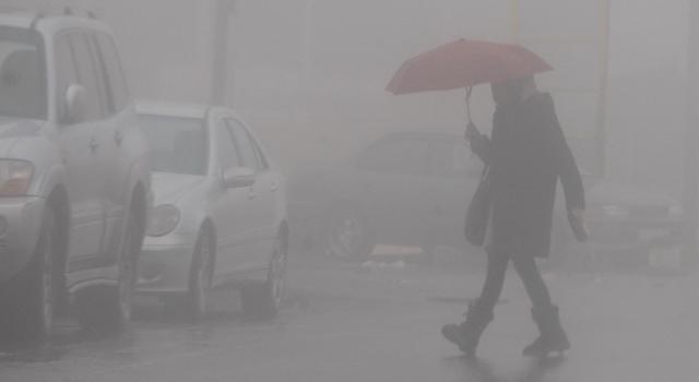 رجل يحتمي بمظلة خلال الأمطار- (أرشيفية- تصوير: أسامة الرفاعي)