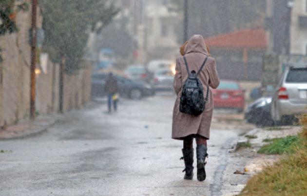 فتاة تسير خلال تساقط الأمطار في إحدى مناطق عمان - (أرشيفية- الغد)