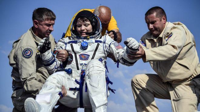 أشخاص يساعدون رائدة الفضاء، آن مكلين، لدى عودتها من محطة الفضاء الدولية في يونيو/ حزيران الماضي.
