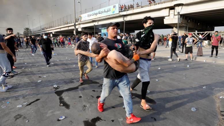 متظاهرون يحملون زميلا لهم بعد إصابته في بغداد (رويترز)