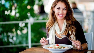 امرأة تأكل طبقاً من السلطة للحفاظ على وزنها