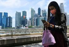 امرأة مستغرقة في تفحص هاتفها المحمول أمام عدد من ناطحات السحاب في سنغافورة