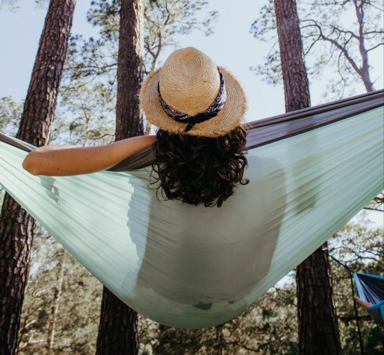 woman with curly hair and straw hat relaxing on hammock