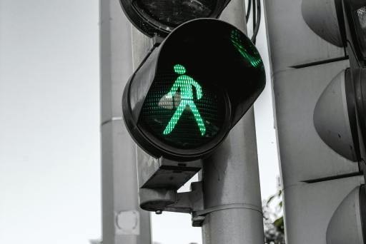 green walk sign on gray city background