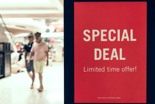 Red deal sign with walking customers