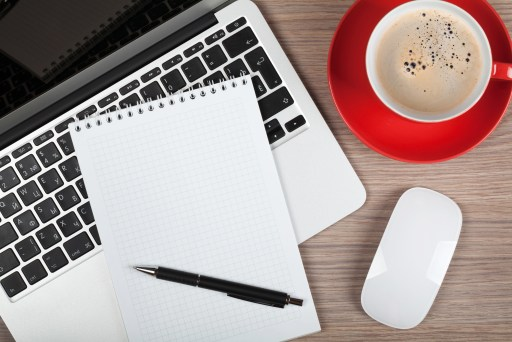 Blank notepad over laptop and coffee cup