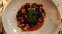 Linguini al nero di seppia con rana pescatrice, pomodori ciliegino e zucchine