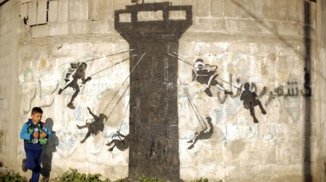 a_child_in_beit_hanoun_walks_past_a_mural_february_2015_that_depicts_children_using_an_israeli_tower_as_a_swing_ride._getty_images
