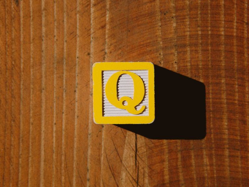 yellow and black card on brown wooden table