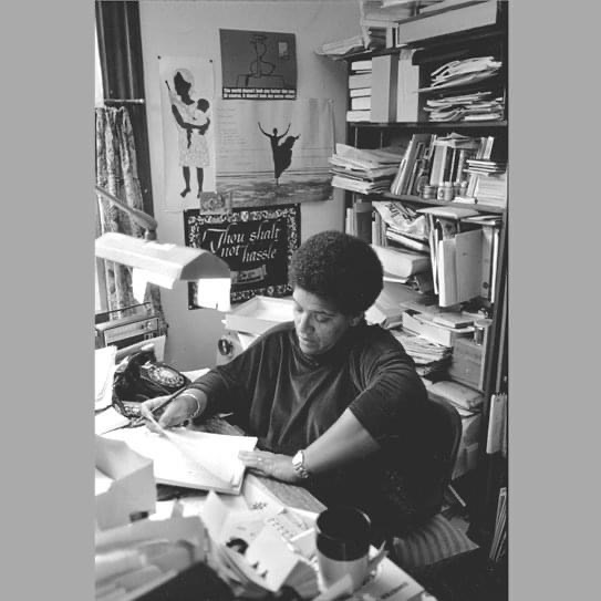 Film photograph of Audre reviewing the final draft of Zami: A New Spelling of My Name, her biomythography in her Staten Island study.