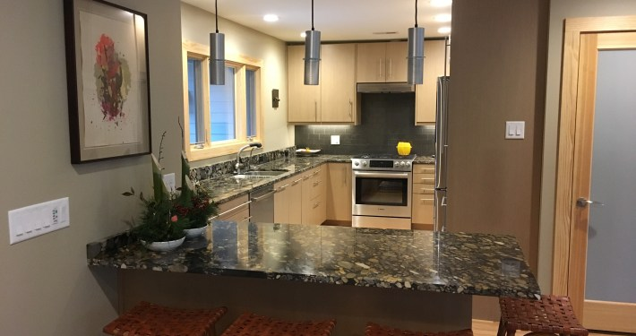 updated kitchen with pendant lights, granite counter, and updated cabinetry