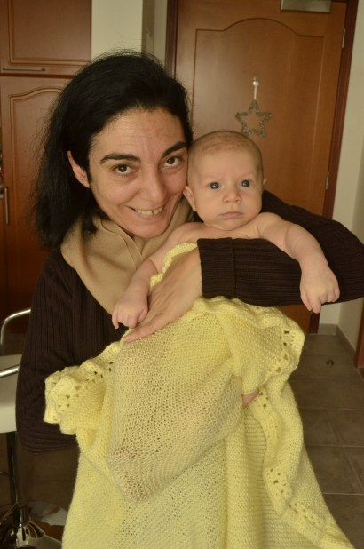 Neighbour and friend Lena with King at 2 months of age, swaddled in the knit he mum sent from Lebanon