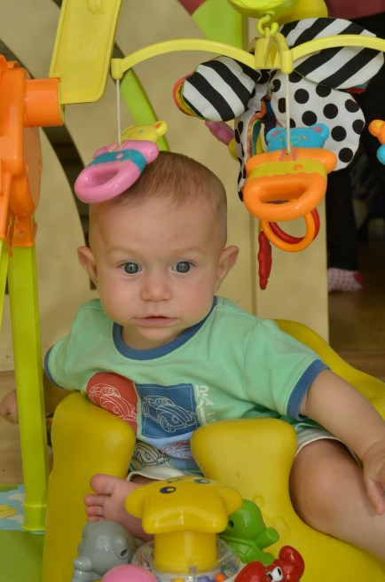 Kingsley surrounded by bright colourful toys, at his nursery