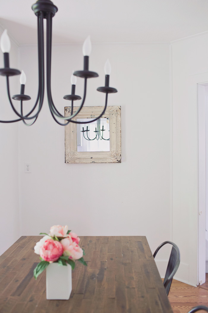 farmhouse dining room with metal chandelier rustic wood table and modern flower arrangment