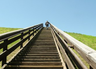 man walks up wooden stairs on a grassy hill