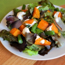 mixed green salad with roasted sweet potatoes and tangy yogurt dressing