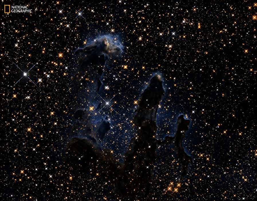 """The Hubble Space Telescope revisited the subject of one of its most iconic images: the Eagle Nebula's """"Pillars of Creation"""". The 2015 image shows the pillars as seen in infrared light, which pierces through obscuring dust and gas to reveal a differe [NASA, ESA AND HUBBLE]"""