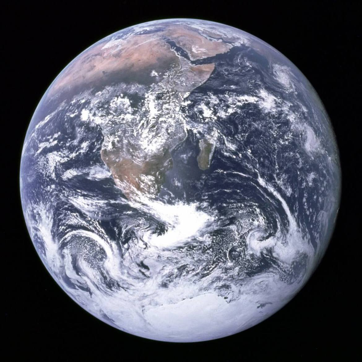 Our planet appears as a brilliant blue marble wrapped in a thin, nearly invisible veil of gas.
