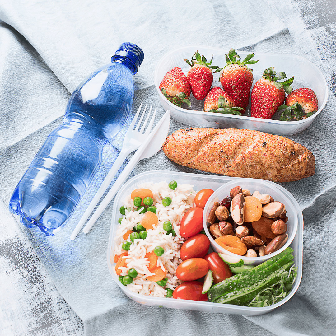 packed lunch with sandwich, strawberries, rice, nuts and a bottle of water