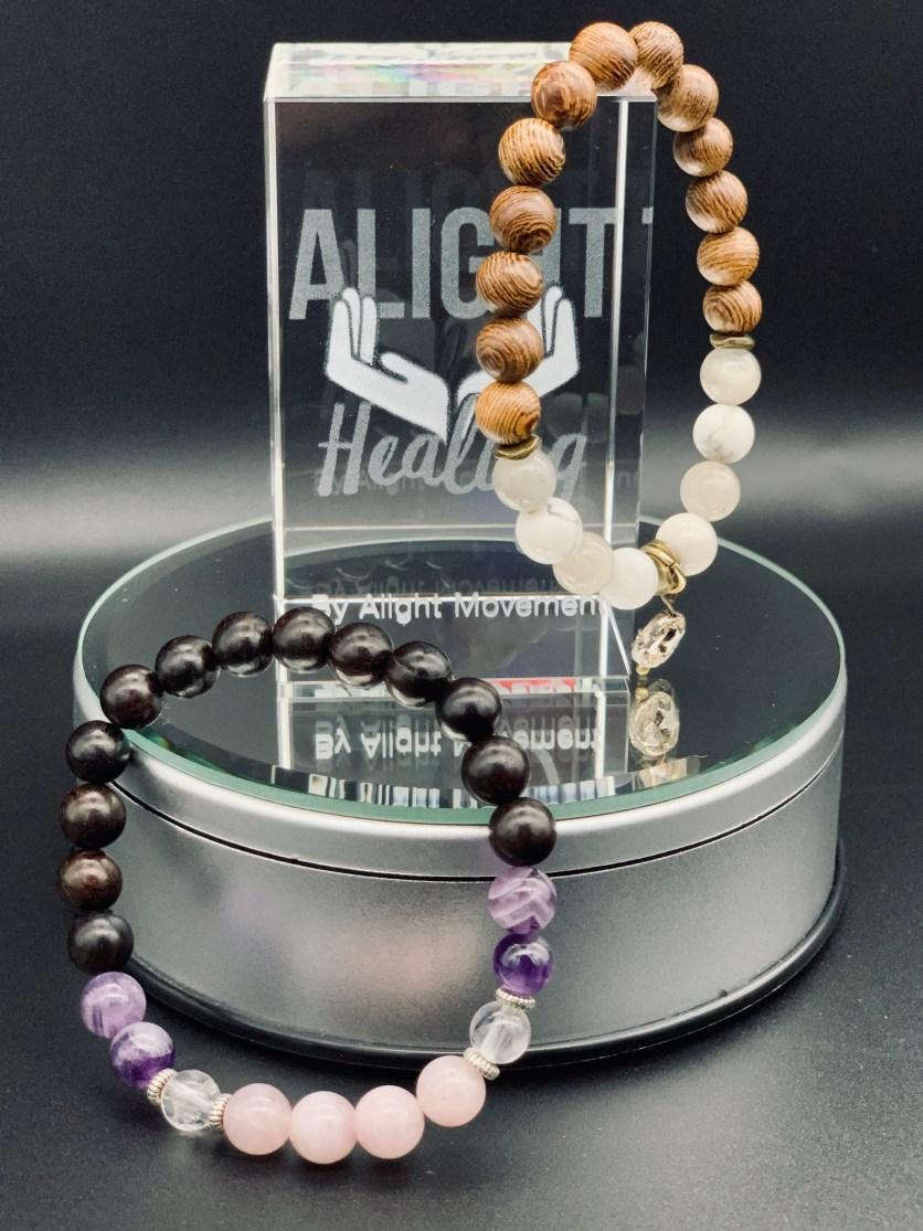 gemstone bracelets and glass that says alight healing by alightmovement