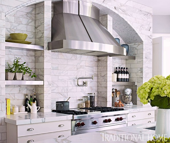 A Wolf Rangetop Anchors Artistic Tile's Calacatta Gold Marble with Stainless Steel Shelves
