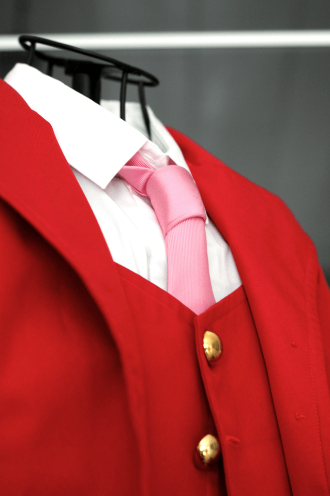 Red jacket, red vest, golden buttons, white shirt and pink tie