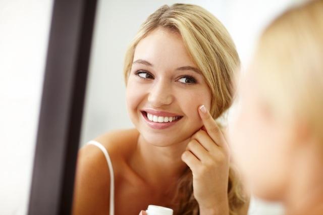 mujer joven limpiando la piel de su rostro