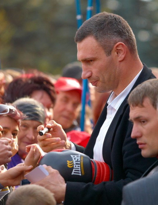 Vitaly Klitschko preparing to sign a boxing glove
