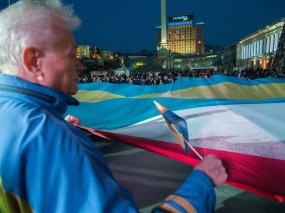 Old man holds the flags of Ukraine and Crimea stitched together
